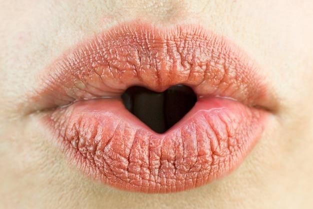 ハートの形をした女性の唇。愛、セクシュアリティ、幸福の概念。