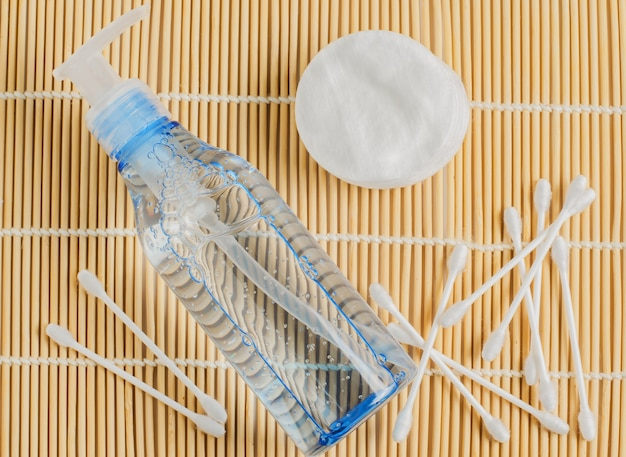 Women's makeup remover accessories. gel in a transparent bottle, cotton buds, cotton pads on bamboo mat