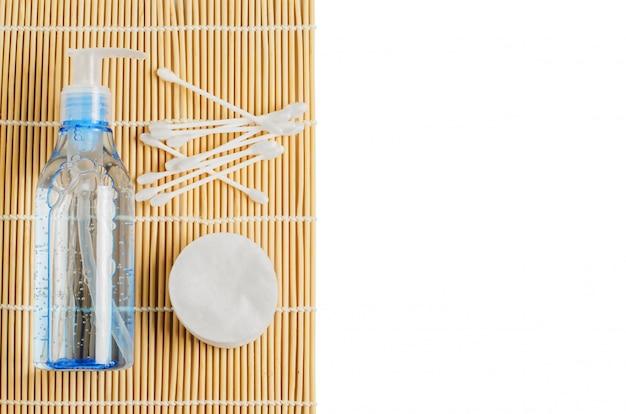 Women's makeup remover accessories. gel in a transparent bottle, cotton buds, cotton pads. copy