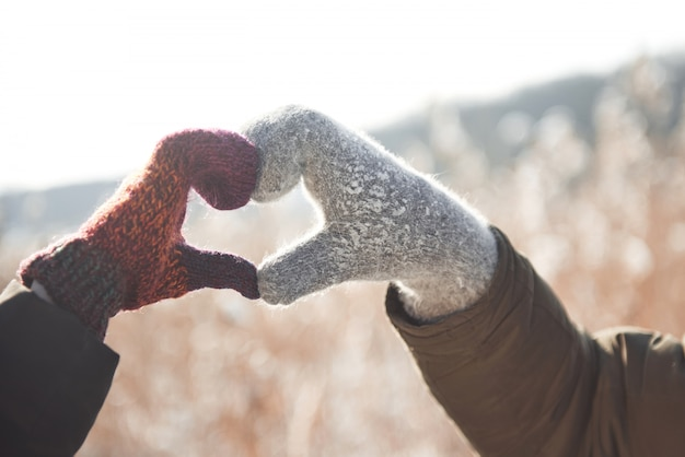 Women's and mans hands in glove folded in heart shape. winter concept. snowfall.