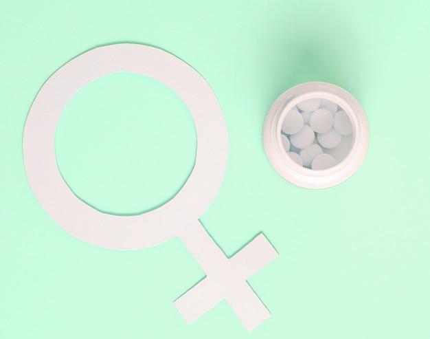 女性の薬のミニマルな概念。白い錠剤、青い背景の上の女性の性別記号のボトル。