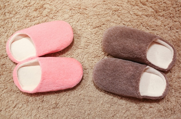 Women's and men's slippers standing on the carpet. two pairs of house shoes.