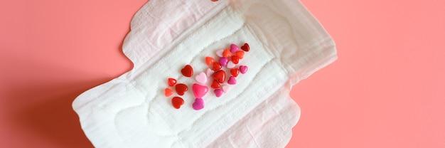 분홍색 배경에 혈액을 모방 한 하트 모양의 빨간색과 분홍색 구슬이있는 분비물의 정상적인 풍부함을위한 여성용 생리대 또는 냅킨.