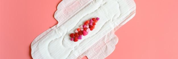 血液の模倣としてハートの形をした赤いビーズで分泌物を正常に豊富にするための女性の月経生理用ナプキンまたはナプキン