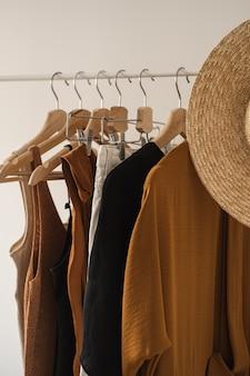 Women's minimal fashion pastel clothes. stylish female blouses, t-shirts, tops, straw hat on clothing rack on white