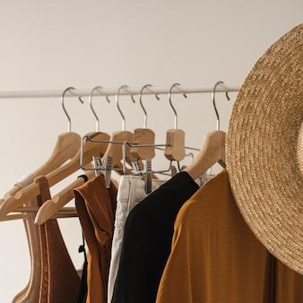 女性のミニマルなファッションパステル服。スタイリッシュな女性のブラウス、tシャツ、トップス、白の衣類ラックに麦わら帽子