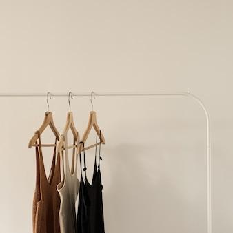 Women's minimal fashion pastel clothes. stylish female t-shirts, tops on clothing rack on white