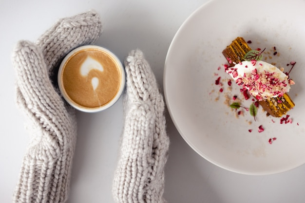 Women's mittened hands hold a coffee mug and a cake next to it on a white table close up. top view. christmas background. concept of winter, warmth, holidays, events.