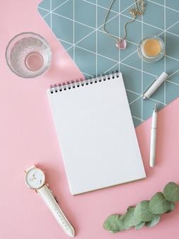 女性のノートのモックアップ。垂直フラットは、ピンクの背景にノート、時計、水のガラスとモックアップを置きます。