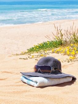 Женская панамская шапка с солнцезащитными очками на полотенце на пляже летом.
