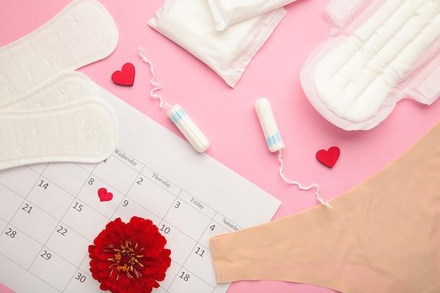 생리대와 탐폰이 분홍색 배경에 있는 여성용 팬티. 평면도. 중요한 날, 월경, 여성 위생의 개념. 평면도