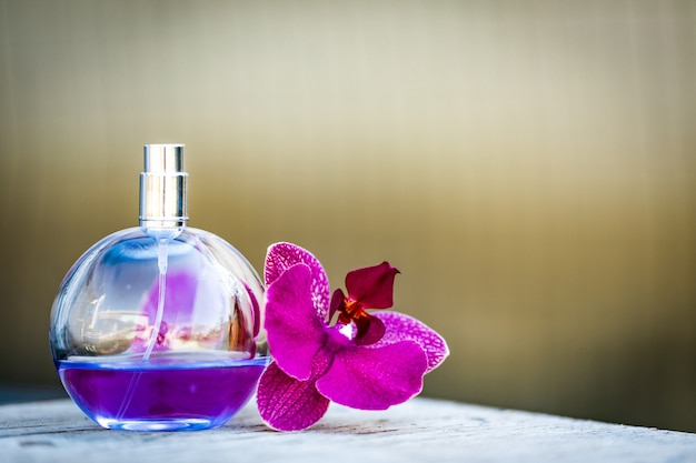 Women's perfume in beautiful bottle with orchids on bokeh background.