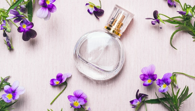 Women's perfume bottle and violets flowers on pink background