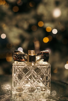 Women's perfume on a glass table with water drops on the background of a christmas tree with lights and bokeh
