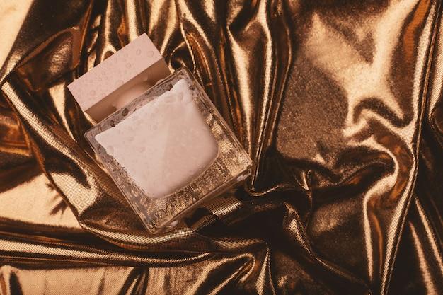 Women's perfume on gold fabric