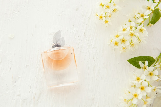 아름다운 병에 든 여성용 향수와 흰색 바탕에 새 체리 꽃. 여성용 플랫 레이 도구 및 액세서리