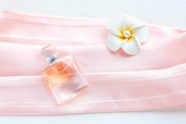 아름다운 병에 든 여성용 향수와 분홍색 배경에 꽃. 실크 핑크 둥근 머리띠 흰색 절연입니다. hair scrunchie와 같은 평평한 평지 미용 도구 및 액세서리,