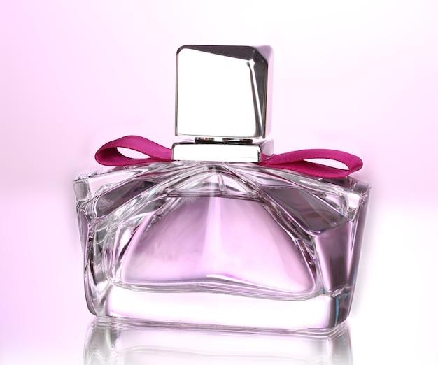 분홍색 표면에 아름다운 병에 여성 향수