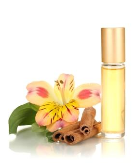 花とシナモンが白で隔離の美しいボトルの女性の香水