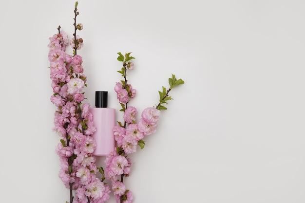 Женский парфюм в красивом розовом флаконе на белом фоне