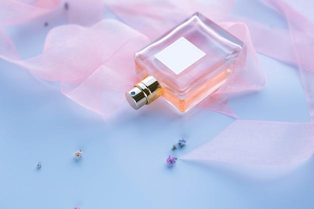 青い背景の上の女性の香水 Premium写真