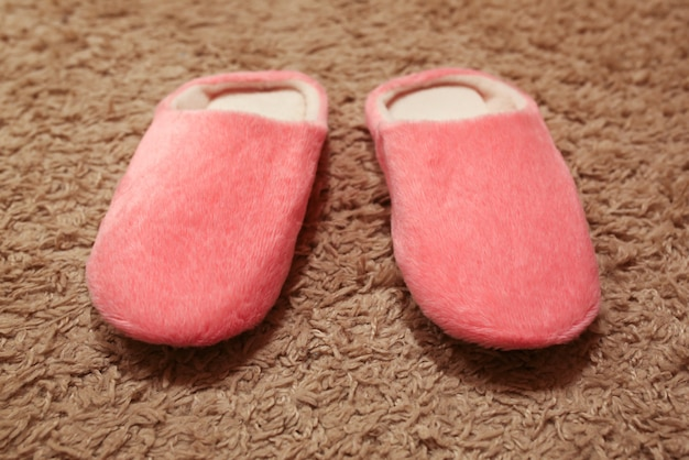 Women's pink slippers standing on the carpet. house shoes.