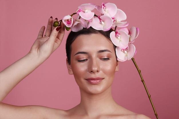 ピンクの蘭、美しさの概念を持つ女性の肖像画