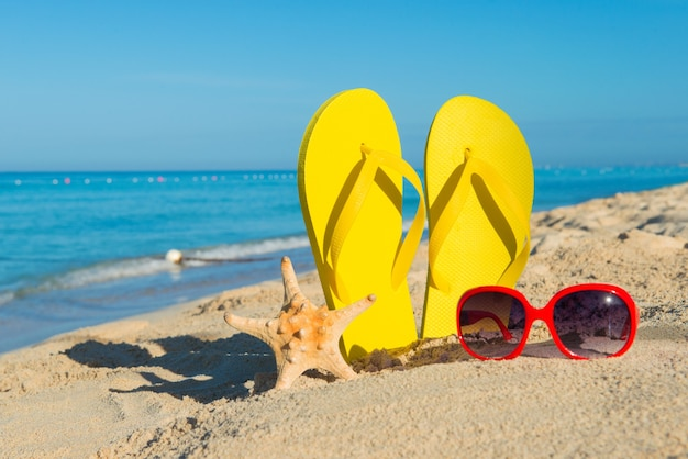 砂浜の海岸にある女性用の赤いサングラスと黄色のビーチサンダル。海で旅行します。ビーチでの休暇