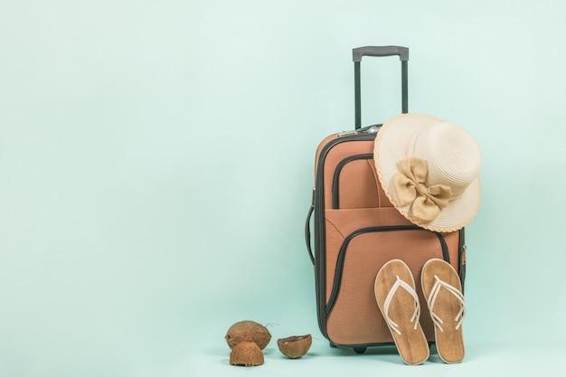 파란색 배경에 손잡이가 달린 여성용 샌들, 모자, 여행가방. 텍스트를 위한 공간입니다.