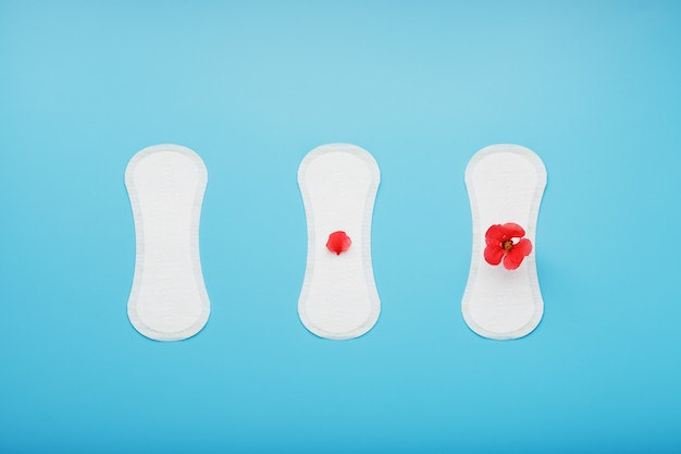 Women's sanitary pads on blue. the concept of critical days, menstrual cycles in several stages.