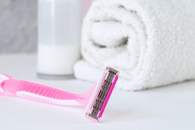 Women's shaving razor with shampoo, towel and antiperspirant on the bathroom