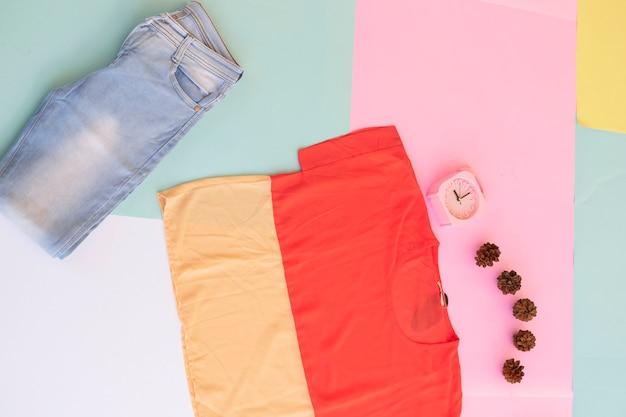 다양한 색상의 파스텔 배경에 여성용 셔츠, 청바지, 갈색 지갑, 검은색 핸드백. 패션 배경 개념