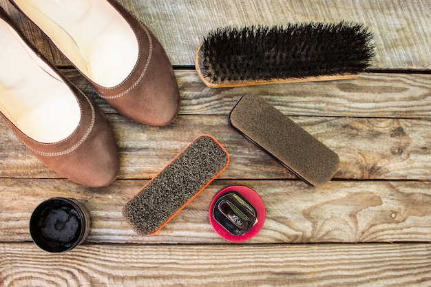 Women's shoes and care products for footwear on wooden background.