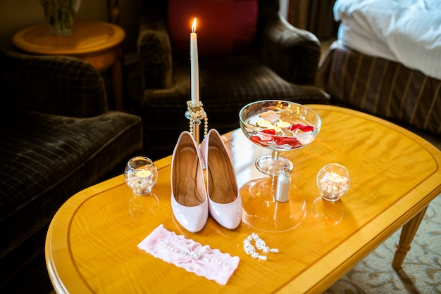 Women's shoes, earrings and candle