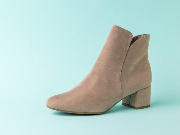Women's suede shoe on a light blue surface