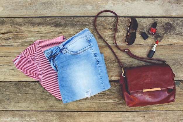 Women's summer clothing and cosmetics on old wooden background. toned image.