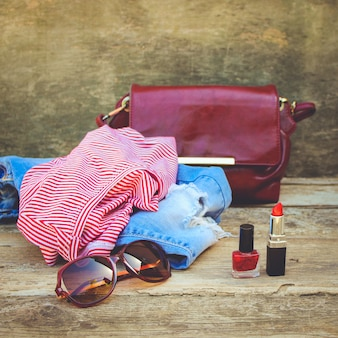 Women's summer clothing and cosmetics on old wooden background