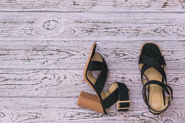 Women's summer shoes of original design on a wooden surface