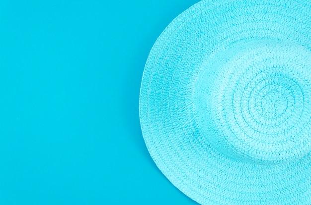 パステルブルーの背景に女性の夏の麦わら帽子