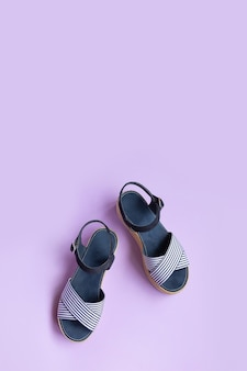 Women's summer striped blue sandals on lilac background with copy space. view from above. vertical photo