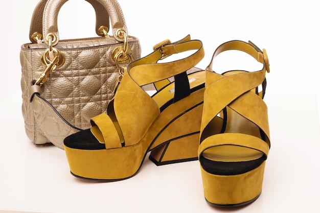 Женские летние желтые кожаные сандалии с гламурной сумочкой на белом изолированы.
