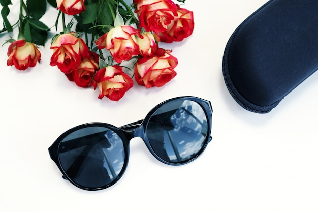 Women's sunglasses on white background with roses and case. optics store, protect your eyes from uv light.