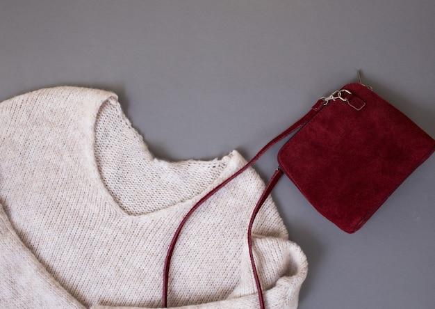 Женский свитер, красная бархатная сумка на сером фоне, вид сверху место для текста