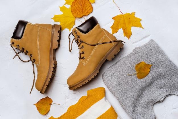 秋のカエデの葉と女性のセーターとブーツ