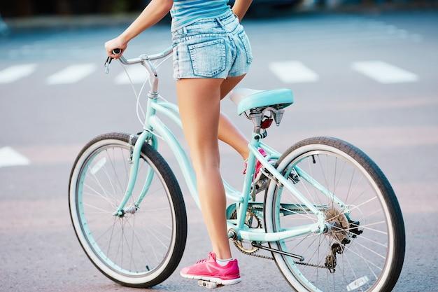 공원에서 복고풍 자전거를 타고 분홍색 운동화를 입고 여성의 황갈색 다리, 복사 공간, 모션 사진.