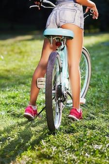 공원에서 푸른 잔디에 복고풍 자전거와 함께 서 분홍색 운동화를 입고 여자의 황갈색 다리 공간을 복사합니다.