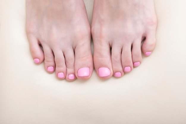 Women's toes close-up. pink pedicure. white