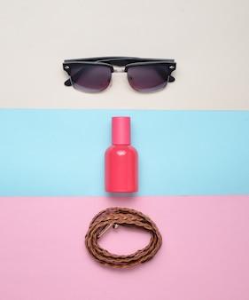 色とりどりのパステル調の背景に女性のトレンディなアクセサリー。メガネ、香水、革ベルト。上面図。ミニマリズム。