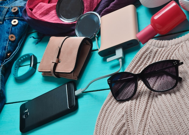 Women's trendy accessories, shoes, clothes and modern gadgets on a blue wooden background. jeans, bag, sneakers, smartphone, smart bracelet, power bank, cosmetics, sunglasses, scarf.
