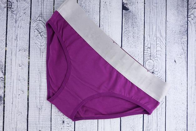 Женское нижнее белье фиолетовые трусики на деревянном
